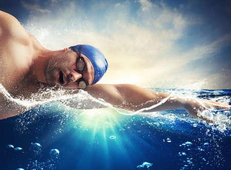 햇빛을 받아 바다에서 헤엄 치는 사람 수영