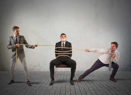 Businessmen hold tied one of their colleagues