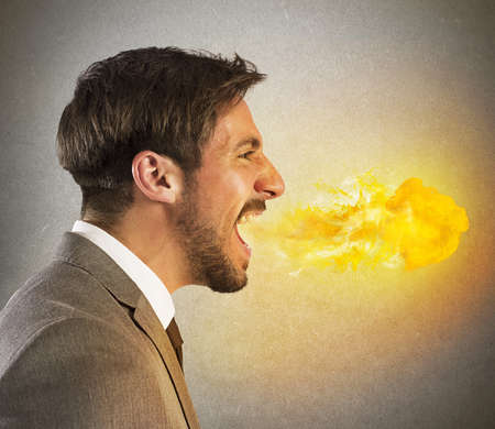 aggressive: Aggressive businessman spits fire from his mouth Stock Photo