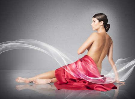 mujer desnuda sentada: Mujer cubierta únicamente por un velo rojo Foto de archivo