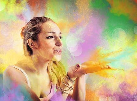 Fille soufflant la poussière colorée comme un arc-en- Banque d'images