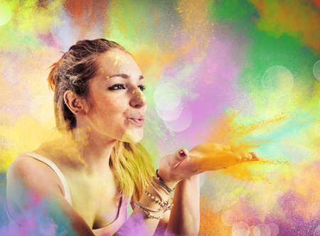 Girl blowing dust colored like a rainbow Stock Photo