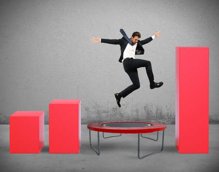 Businessman jumps on the trampoline between statistics