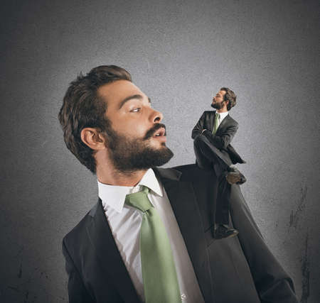 malignancy: Businessman with small himself in the shoulder Stock Photo