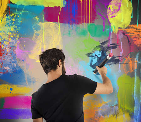 creativeness: Creative boy colors with pencil a wall