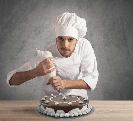 homme: Pâtissier prépare un gâteau au chocolat et à la crème