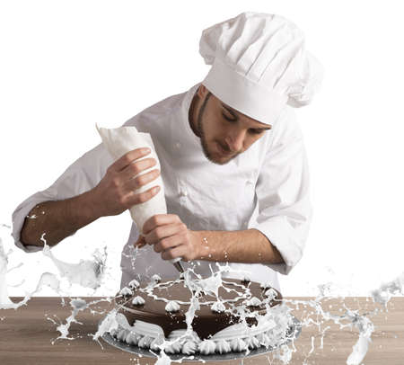 Pastry chef decorates a cake with cream