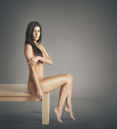 Nude model sitting on a wooden table Stock Photo