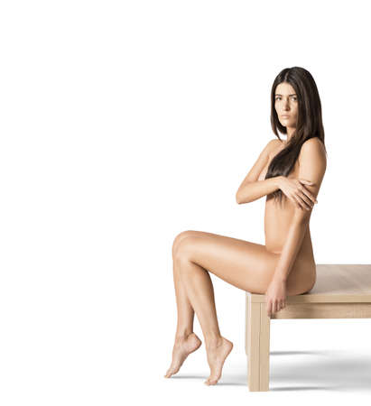 mujer desnuda sentada: Modelo desnuda sentada en una mesa de madera Foto de archivo