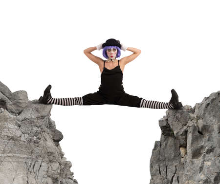exertion: Clown dancer makes split between two mountains