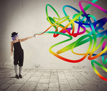 paints: Woman clown with colored spray paints trails Stock Photo