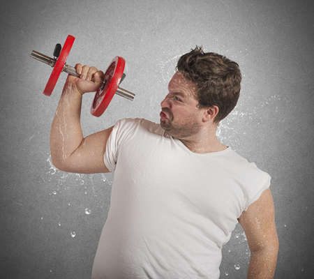 Fatigued fat man sweats while lifting weights