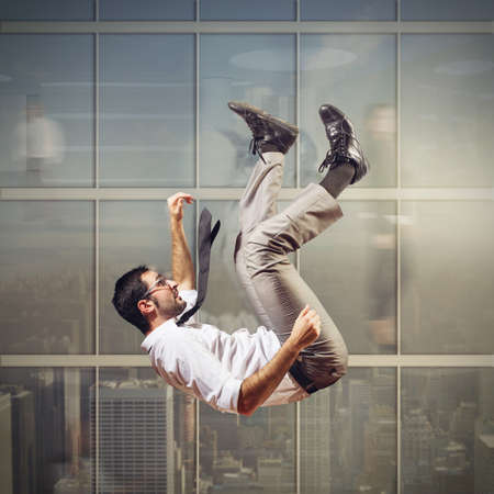 hombre cayendose: El hombre de negocios se apresura abajo de un rascacielos