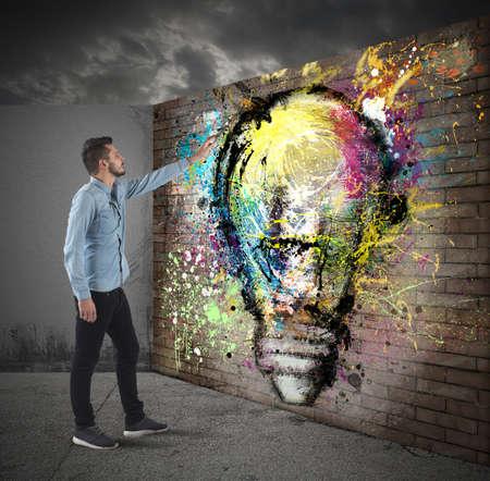 creativity: Boy draws a colored bulb on a wall Stock Photo