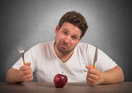 eager: Sad fat man eating only an apple Stock Photo