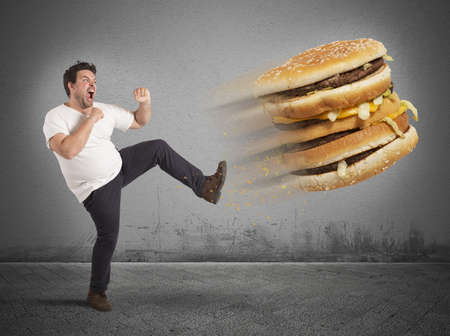 the calories: Fat man kicks a giant fat sandwich Stock Photo