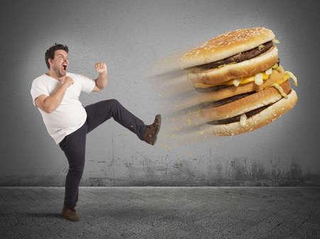 Homem gordo chuta um sanduíche gigante de gordura Foto de archivo