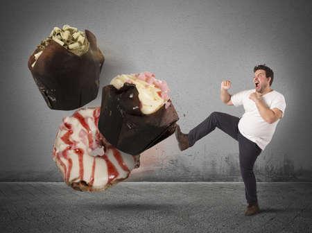high calorie: Fat man kicks a high calorie sweet
