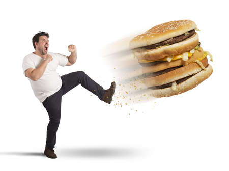 corpulent: Fat man kicks a giant fat sandwich Stock Photo