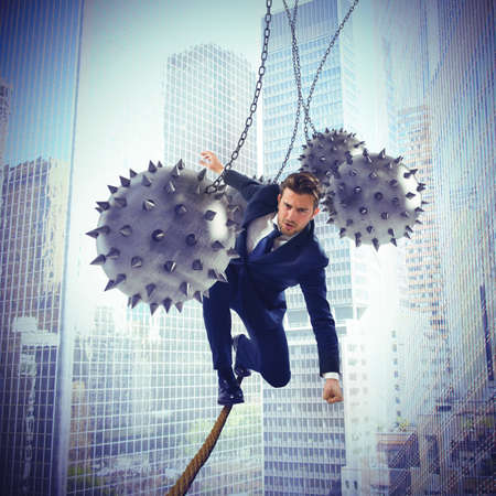 Businessman hindered by balls balanced on rope