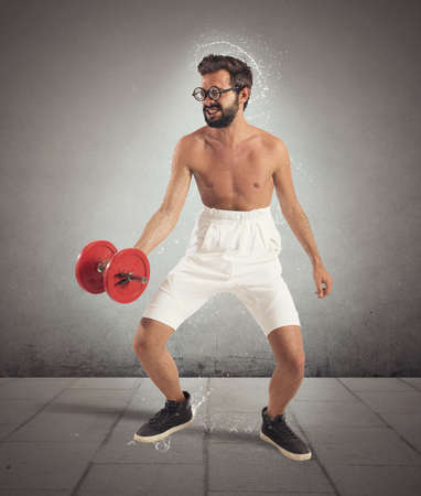 eccentric: Nerdy guy and awkward lifts of weights Stock Photo