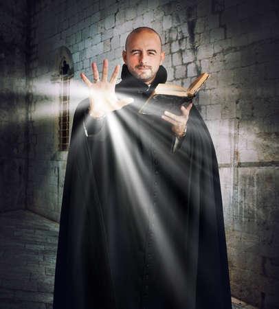 sotana: Sacerdote con la Biblia emite luz