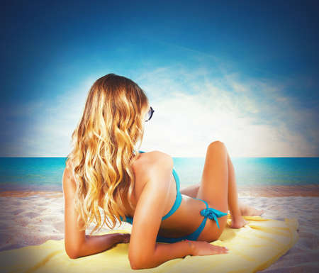 girl with towel: Girl in bikini sunbathing at the beach Stock Photo