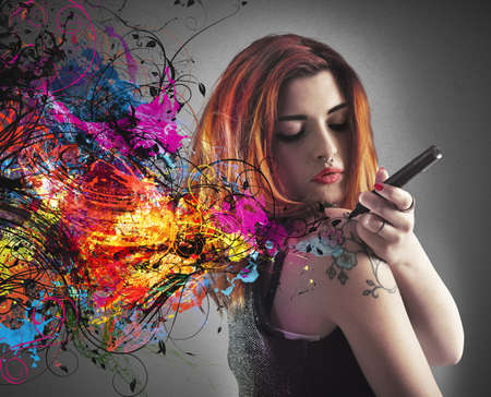 artistas: La muchacha drena un tatuaje en su brazo