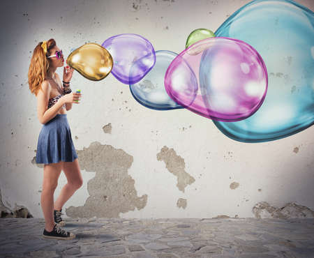 blows: Girl has fun making colorful soap bubbles Stock Photo