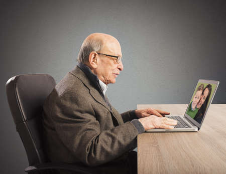 distant: Grandpa talking with distant family with webcam Stock Photo