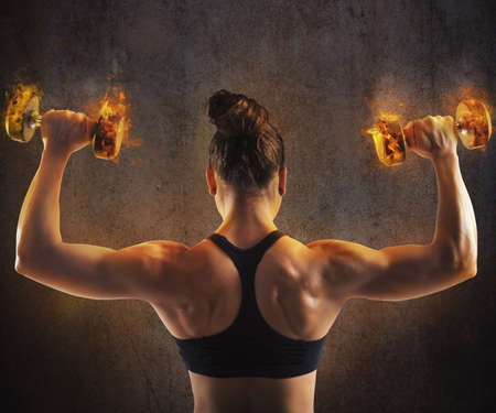 muscle women: Gym woman train back with fiery dumbbells Stock Photo