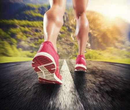 アスファルトの上を実行しているスポーティな女性の足