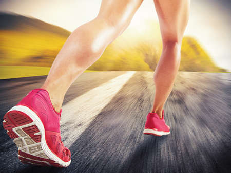 in action: Legs of sporty woman running on asphalt Stock Photo