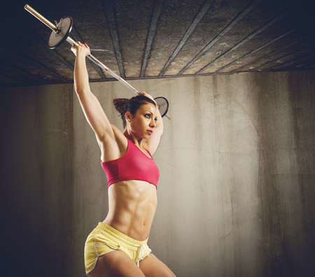 woman muscle: Muscular woman doing hard workout with barbell Stock Photo