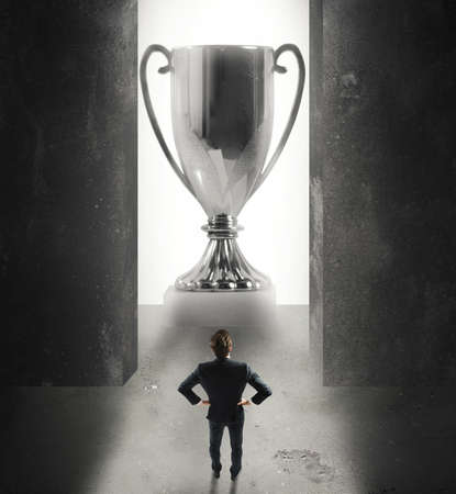 destinations: Winner businessman in front of a giant cup Stock Photo