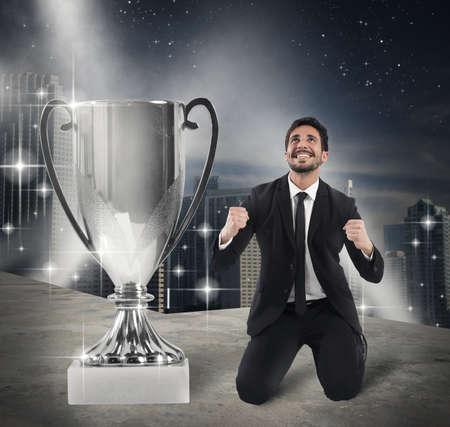 exult: Businessman kneeling exult in front of cup Stock Photo