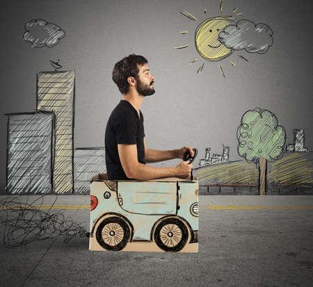 Jongen rijden kartonnen auto bij het opstellen stad