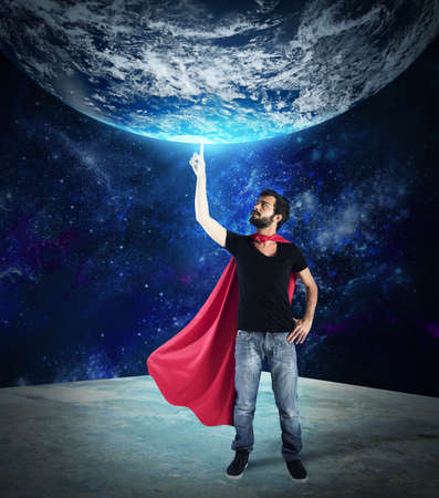 invincible: Superhero holds the world with a finger Stock Photo