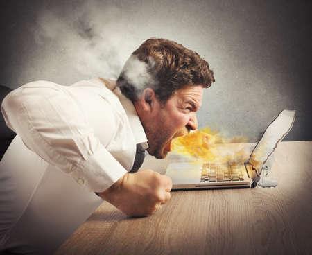 Zakenman spuwt vuur en smelt de computer Stockfoto