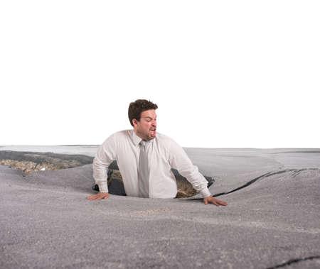 Businessman alone and afraid swallowed by asphalt