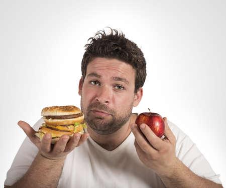 Hombre indeciso entre la dieta y la comida chatarra