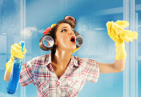 Pin-up housewife breathes on a clean glass Stockfoto