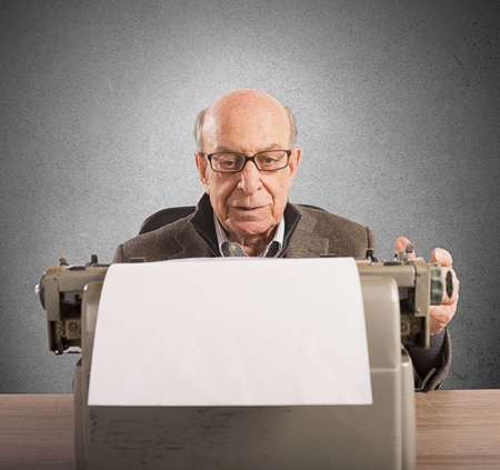 letter writing: Old man writes letters with his typewriter Stock Photo