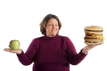 personas comiendo: Mujer indecisa si desea iniciar la dieta Foto de archivo