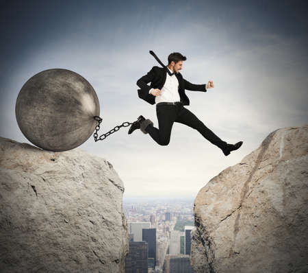 businessman jumping: Businessman jumping with ball tied to foot