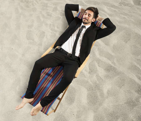 Businessman relaxes lying on a beach chair