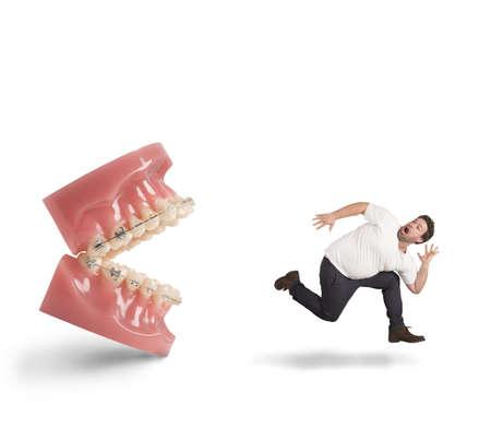 dental fear: Man runs away for fear of dentist Stock Photo