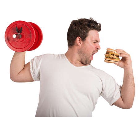 Fat man lifts weights eating a sandwich