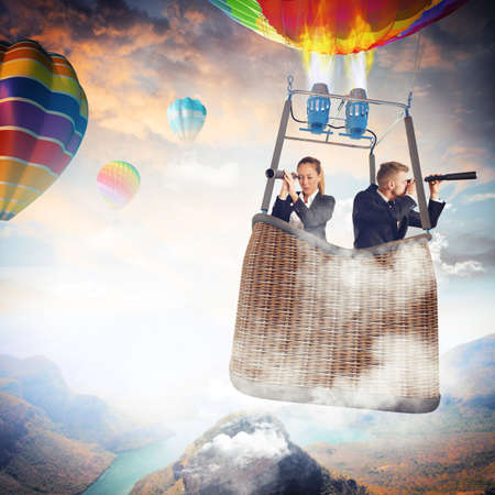 Businesspeople with binoculars in hot air balloon