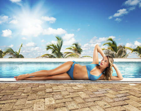 Girl in bikini sunbathes lying on poolside